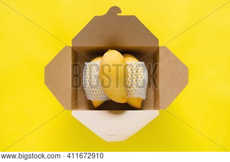 Ripe Yellow Thailand Barracuda Mangoes With Foam Mesh Put In Paper Box On Yellow Background.