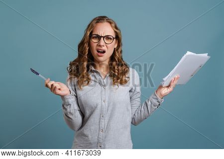 Angry irritated young business woman isolated over blue background, holding clipboard