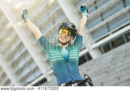 Portrait Of Successful Professional Female Cyclist In Cycling Garment Raised Her Arms, Smiling At Ca