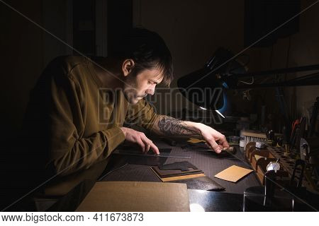European Male Tanner Working On Workplace With Leather Make Wallet. Handmade In A Small Manufactory.