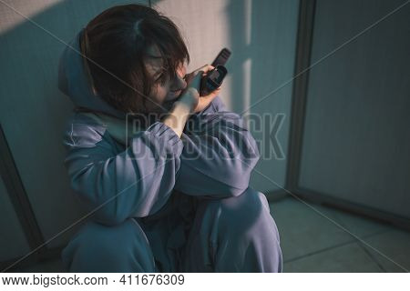 Upset Woman Sitting On The Floor In The Dark, Holding A Gun And Crying After Committing Murder In Se