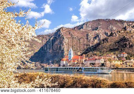 Durnstein Village During Spring Time With Tourist Ship On Danube River In Wachau, Austria