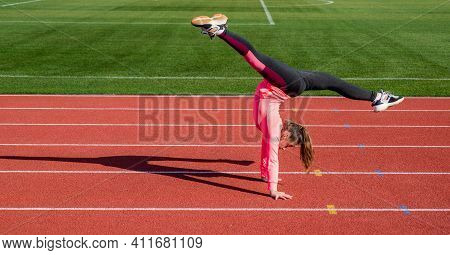 Workout On Fresh Air. Confident Gymnast With Flexible Body. Gymnastics. Teen Girl Do Trick On Stadiu