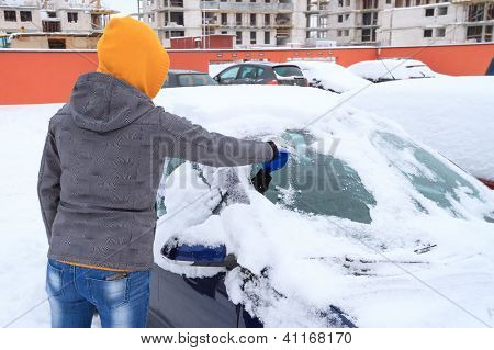 Woman scraping ice from the car window in winter time