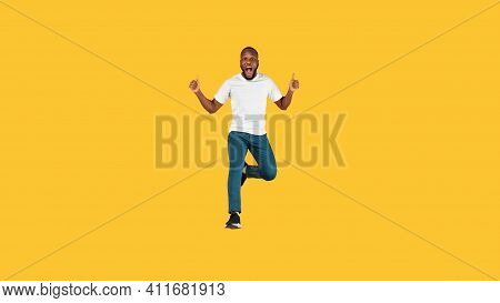 I Like It. Emotional Black Guy Jumping Gesturing Thumbs Up In Excitement Posing In Mid-air Over Yell