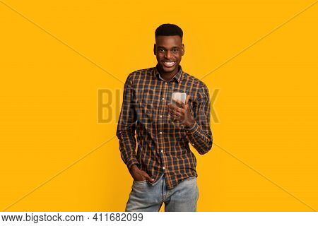 Portraif Of Handsome Young African American Guy With Smartphone In Hands Posing Over Yellow Backgrou