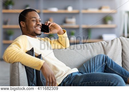 Communication Concept. Relaxed African American Man Sitting On Sofa In Living Room, Having Conversat