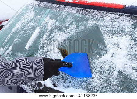 Hand scraping ice from the car window in winter time