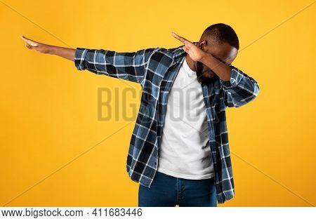 Black Guy Throwing Dab Gesture Having Fun Posing Standing On Yellow Studio Background. African Ameri