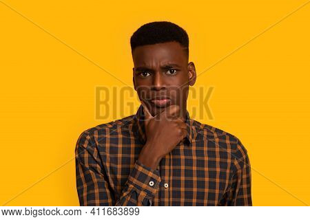 Portrait Of Young Interested Black Guy Touching Chin, Thinking About Offer, Curious African American