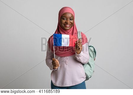 Positive Black Woman In Hijab Showing Flag Of France, Carrying Backpack On Shoulder, Grey Studio Bac
