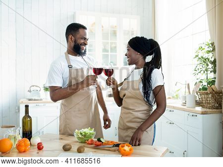 Romantic Black Spouses Drinking Red Wine While Cooking Tasty Lunch At Home Together, Cheerful Africa