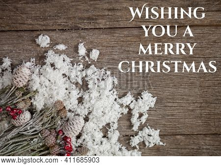 Wishing you a merry christmas text with christmas decoration on wooden background. christmas greetings, celebration and festivity concept digitally generated image.