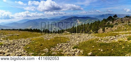 Green High Mountain Landscape In The Spanish Pyrenees. Big Mountains, Clouds And Blue Sky In An Atmo