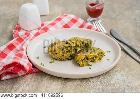 Fried Burgers Or Cutlets Of Bulgur, Carrots And Spinach On A Light Ceramic Plate On A Gray Concrete