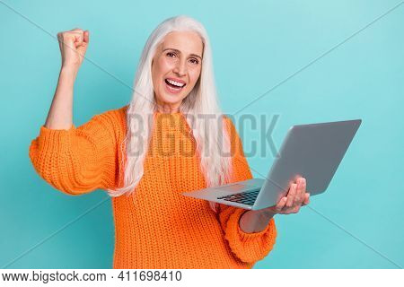 Photo Of Cheerful Positive Happy Old Woman Raise Fist Win Hold Computer Isolated On Teal Color Backg