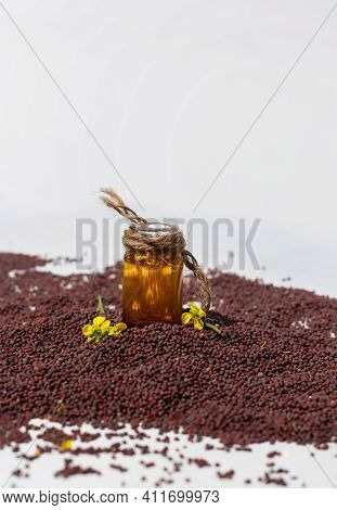 Black Mustard Seed With Mustard Oil In A Small Glass Bottle  And Flower Isolated On White Background