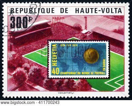 Burkina Faso - Circa 1977: A Stamp Printed In Burkina Faso Shows Soccer Stadium And Swiss Stamp, 11t