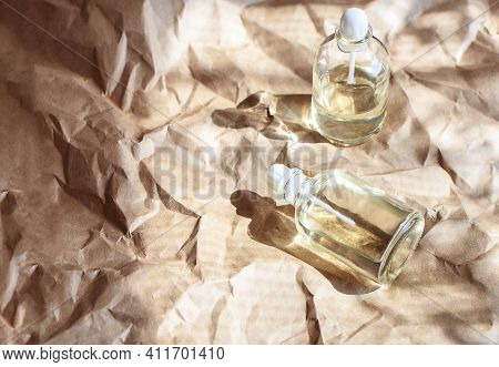 Glass Bottles With Natural Oils On Wrinkled Craft Paper With Its Shadow. Natural Cosmetic Products.
