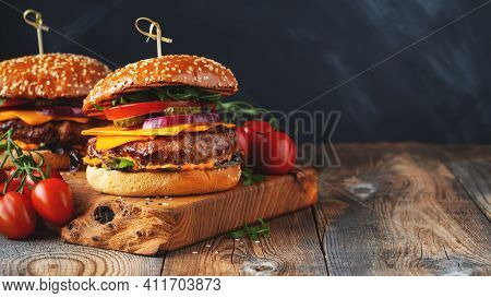 Two Delicious Homemade Burgers Of Beef, Cheese And Vegetables On An Old Wooden Table. Fat Unhealthy