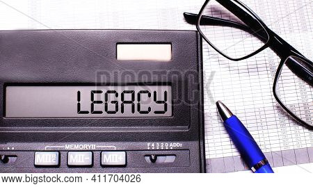 The Word Legacy Is Written In The Calculator Near Black-framed Glasses And A Blue Pen.