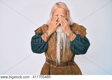 Old senior man with grey hair and long beard wearing viking traditional costume rubbing eyes for fatigue and headache, sleepy and tired expression. vision problem