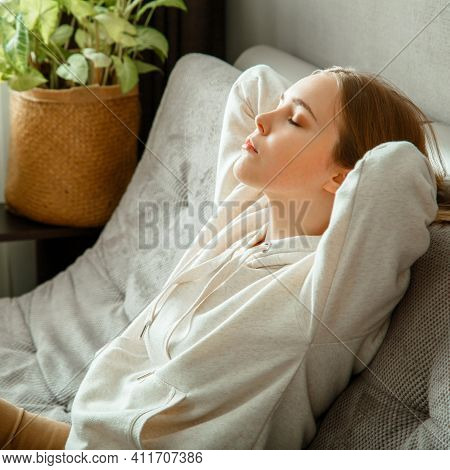 Happy Calm Young Woman Relax Sitting On Comfort Couch At Home Interior. Teen Girl Resting, Bliss Enj