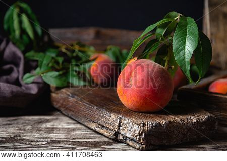 Juicy Ripe Peach On Dark Wooden Rustic Cutting Board. Delicious Farm Peaches With Leaves. Still Life