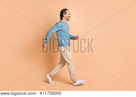 Full Length Profile Photo Of Guy Walk Wear Eyewear Blue Pullover Pants Sneakers Isolated Beige Color