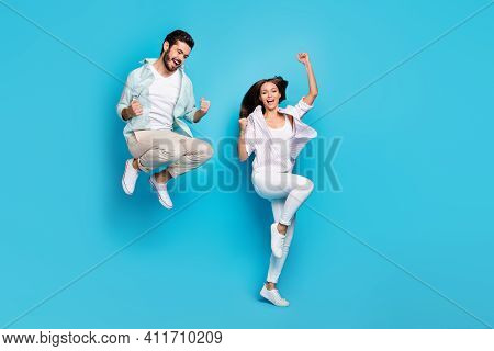 Photo Of Funky Astonished Young Couple Wear Casual Shirt Rising Fists Jumping High Isolated Blue Col