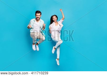Photo Of Funny Lucky Young Lovers Dressed Casual Shirts Jumping High Rising Fists Isolated Blue Colo