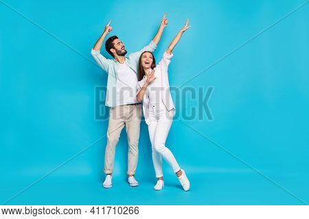 Photo Of Pretty Funky Young Couple Wear Casual Shirt Pointing Empty Space Dancing Isolated Blue Colo