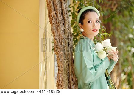 Portrait Of Gorgeous Young Vietnamese Woman In Ao Dai Dress Holding White Lotus Flowes And Looking A