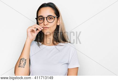 Young hispanic woman wearing casual white t shirt mouth and lips shut as zip with fingers. secret and silent, taboo talking