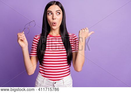 Photo Of Amazed Brown Haired Woman Point Look Empty Space Hold Glasses Advert Isolated On Purple Col