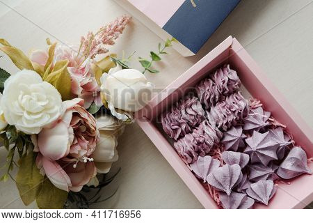 Pink Meringue In A Box And A Bouquet Of Flowers On A White Table