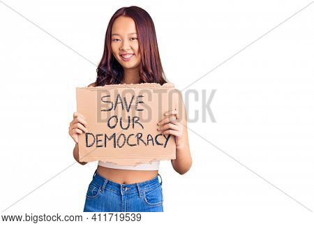 Young beautiful chinese girl holding save our democracy protest banner looking positive and happy standing and smiling with a confident smile showing teeth
