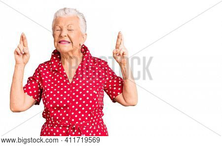 Senior beautiful woman with blue eyes and grey hair wearing a red summer dress gesturing finger crossed smiling with hope and eyes closed. luck and superstitious concept.
