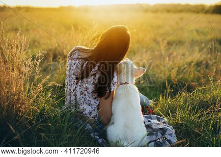 Happy Woman With Cute White Puppy Sitting In Summer Meadow And Looking At Warm Sunset. Happiness