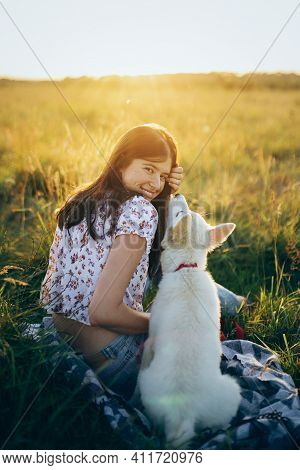 Happy Woman Cuddling With Cute White Puppy In Summer Meadow In  Sunset. Happiness. Summer Vacation