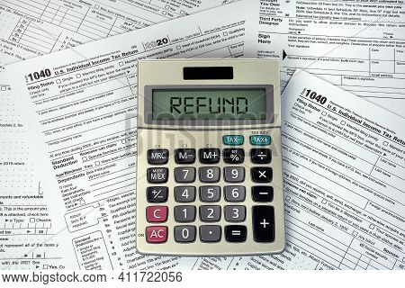 Refund Text On Business Calculator Screen With 1040 Internal Revenue Tax Forms
