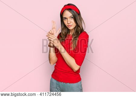 Young brunette woman wearing casual clothes holding symbolic gun with hand gesture, playing killing shooting weapons, angry face