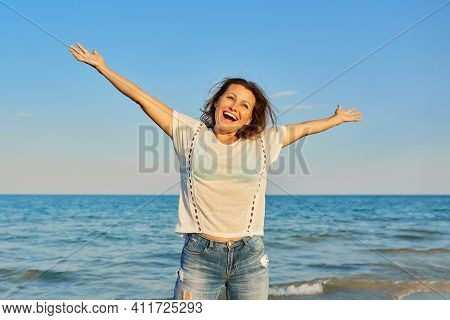 Happy Smiling Mature Woman On The Sea Beach, Positive Female With Arms Raised Up. Happiness, Joy, Re