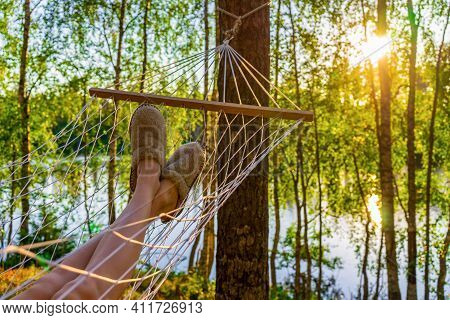 Female Legs In Home Slippers In Hammock Against Beautiful Summer Landscape Of Northern Forest And La