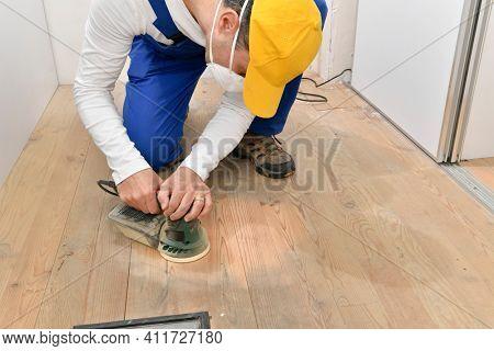 Male carpenter grinding raw wood with orbital sander tool