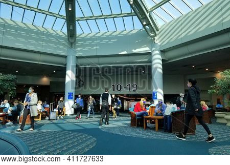 Orlando, Florida, U.s - February 21, 2021 - The Busy Airport Terminal With Passengers Wearing Mask D