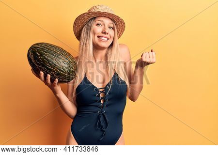 Young beautiful blonde girl wearing swimwear and summer hat holding melon screaming proud, celebrating victory and success very excited with raised arm
