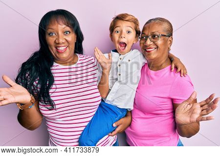 Hispanic family of grandmother, mother and son hugging together celebrating achievement with happy smile and winner expression with raised hand