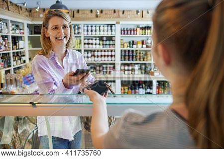 Smiling Female Customer Delicatessen Food Store Making Contactless Payment With Mobile Phone For Sho