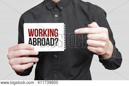 Businessman Holding A Card With Text Working Abroad,business Concept